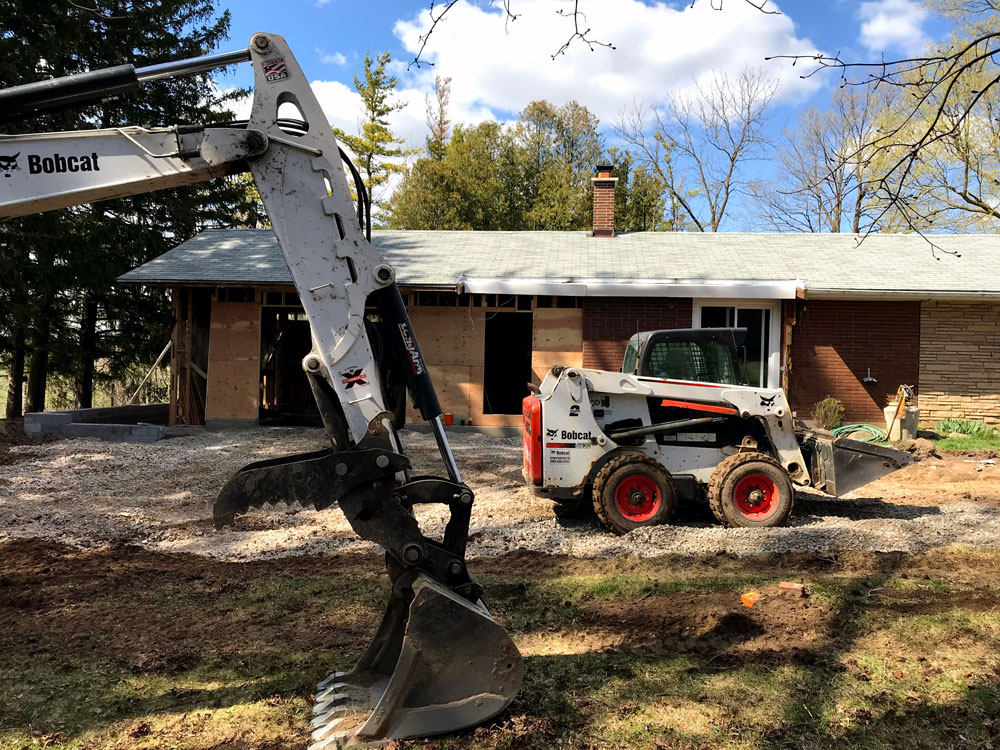 Backhoe and skid steer working on the garage construction